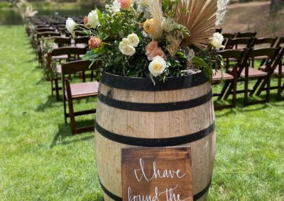 Floral arrangement in a barrel for an outdoor wedding